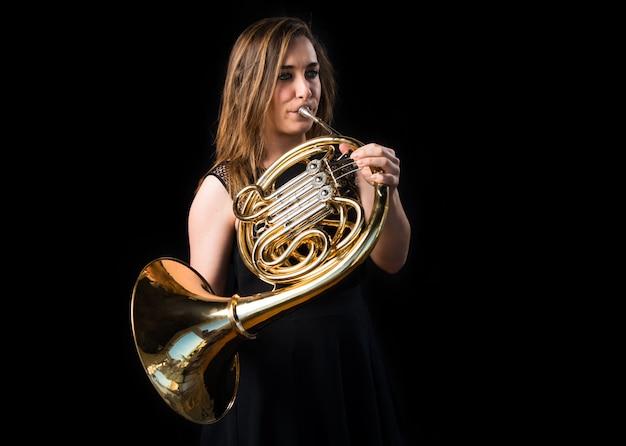 Mädchen, das das französische horn spielt