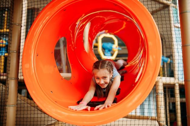 Mädchen, das das labyrinth im kinderspielzentrum klettert