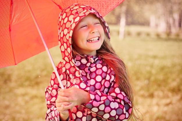 Mädchen, das das regnerische wetter genießt