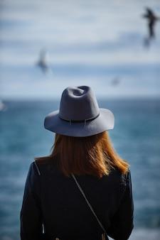 Mädchen, das das ruhige meer auf mit wind in ihren haaren betrachtet