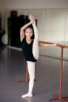 Mädchen, das das strecken in der ballettschule tut.