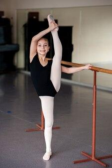Mädchen, das das strecken in der ballettschule tut