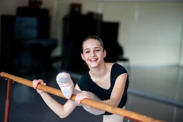 Mädchen, das dehnung in der ballettschule tut.