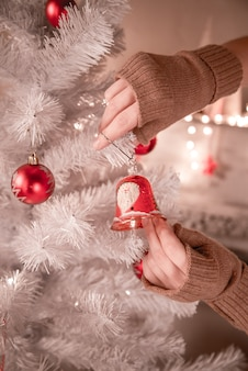 Mädchen, das dekorative spielzeugglocke auf weihnachtsbaumzweig hängt.