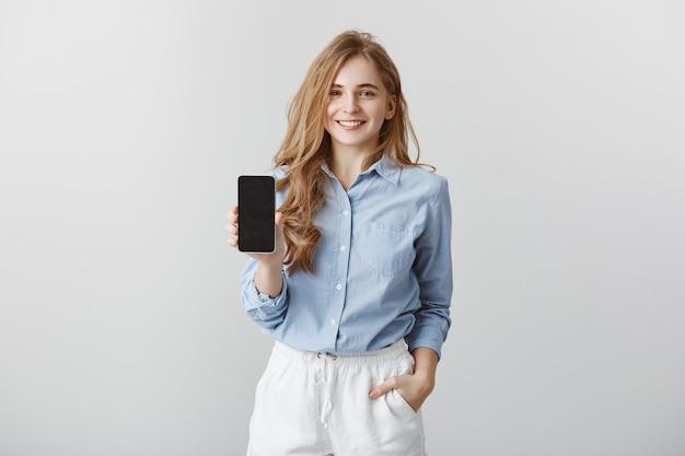 Mädchen, das dem kollegen neues telefon zeigt. porträt des charmanten freundlich aussehenden europäischen modebloggers in der formalen blauen bluse, die hand in der tasche hält, während smartphone über graue wand, werbung zeigt