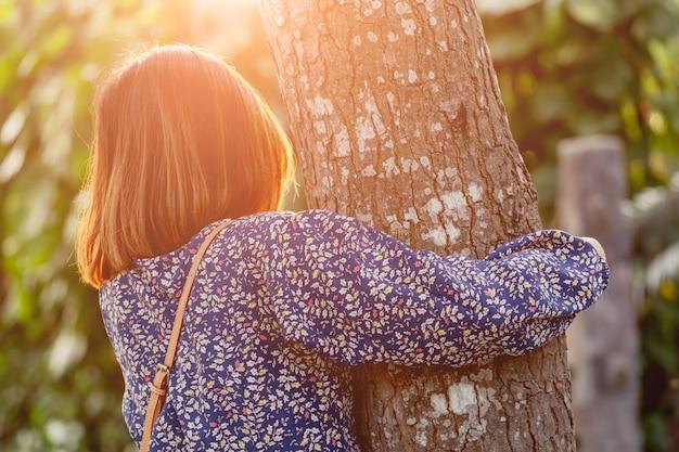 Mädchen, das den baum umarmt