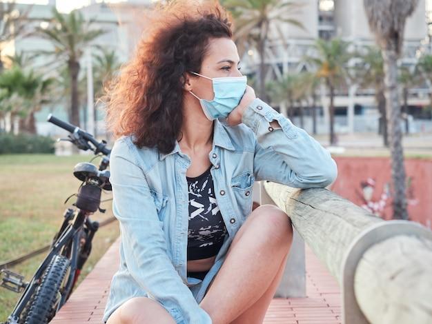 Mädchen, das den horizont mit einer schutzmaske betrachtet, die in einem park nach einer radtour ruht. strand im hintergrund.