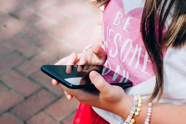 Mädchen, das den smartphone macht bild oder spiel hält