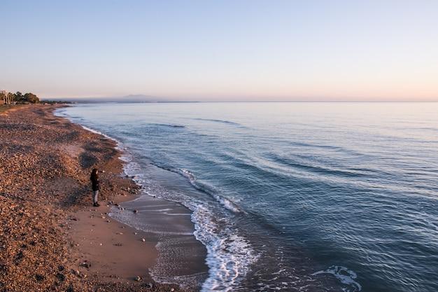Mädchen, das den sonnenaufgang auf dem strand aufpasst