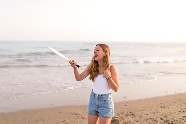 Mädchen, das den tennisschläger lacht über strand hält