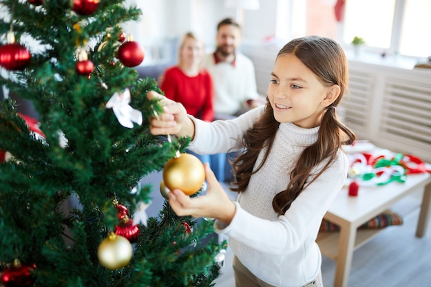 Mädchen, das den weihnachtsbaum verziert