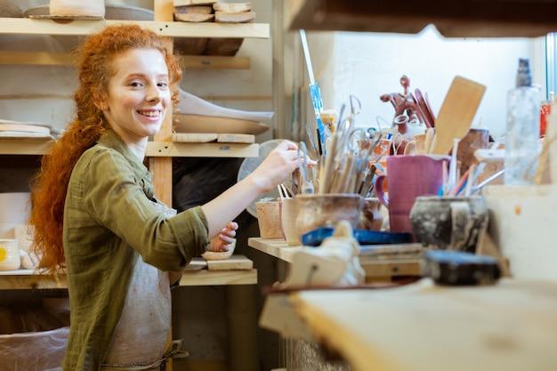 Mädchen, das den zustand überprüft. lächelnder ungewöhnlicher töpfermeister, der werkzeuge für die arbeit auswählt, während er in einem organisierten bereich bleibt