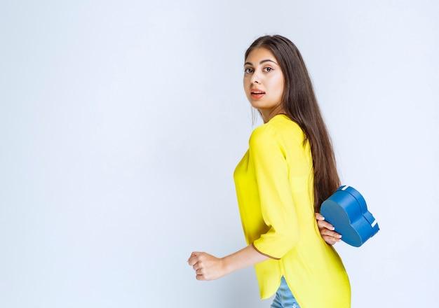 Mädchen, das die blaue herzform-geschenkbox hinter sich versteckt.
