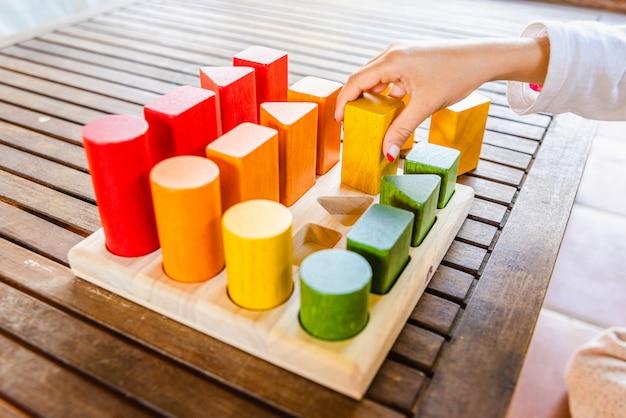 Mädchen, das die blöcke platziert, die ein geometrisches montessori-puzzle der farben