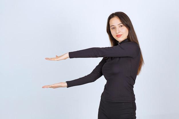 Mädchen, das die geschätzte höhe eines objekts zeigt.