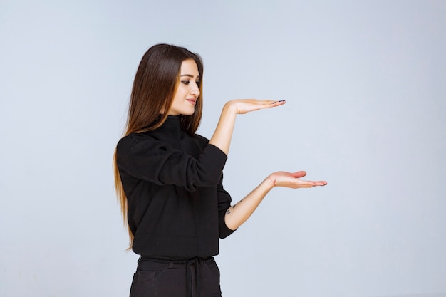 Mädchen, das die geschätzten maße eines objekts zeigt. foto in hoher qualität