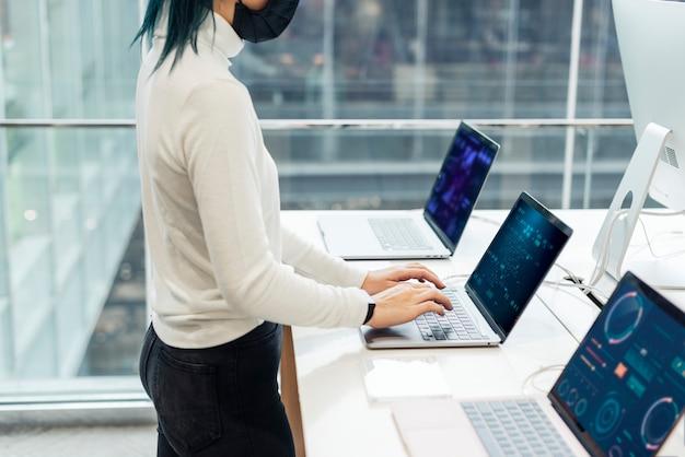 Mädchen, das die laptop-produktschaufenster in einem geschäft prüft