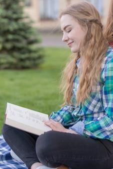 Mädchen, das draußen auf picknickdecke studiert