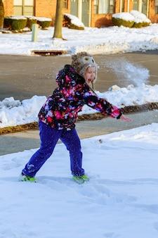 Mädchen, das draußen draußen in den winter geht und mit schnee spielt