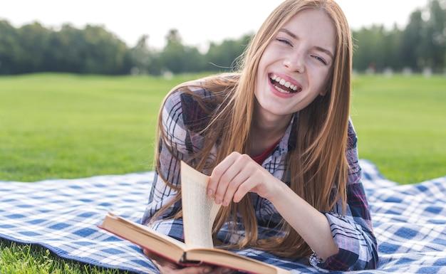 Mädchen, das draußen ein buch auf picknickdecke liest