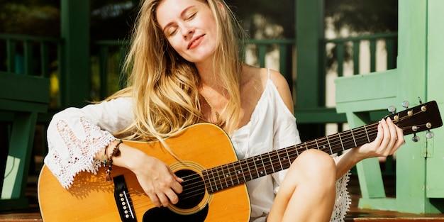 Mädchen, das draußen gitarre-sommer-konzept spielt
