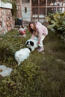 Mädchen, das draußen mit ihren hunden spielt