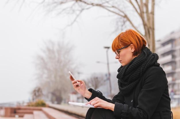 Mädchen, das draußen mobile in der winterzeit verwendet.