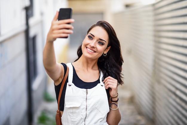 Mädchen, das draußen selfie foto mit intelligentem telefon macht