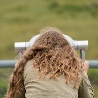 Mädchen, das durch ein münzfernglas, westbach-teich, norris point, gros morne nation schaut