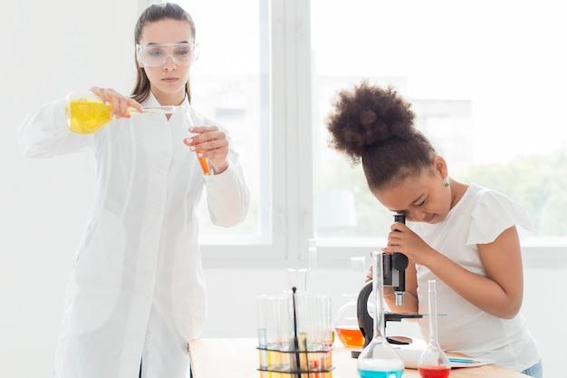 Mädchen, das durch mikroskop mit wissenschaftlerin und tränken schaut
