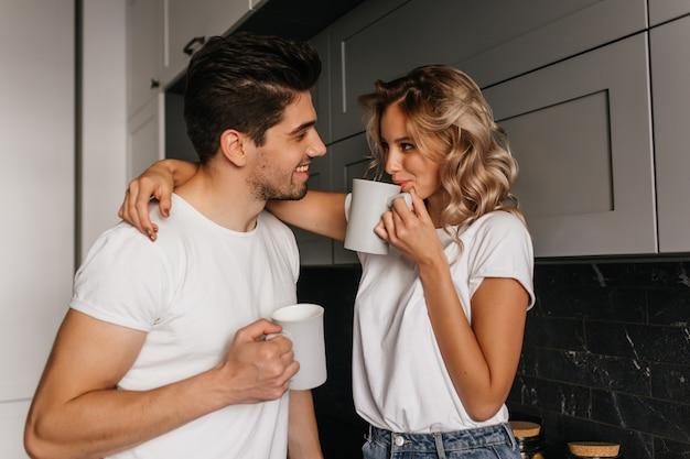 Mädchen, das ehemann spielerisch berührt und kaffee trinkt. innenporträt des romantischen paares, das frühstück zusammen genießt.