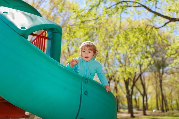 Mädchen, das eichel und buntes blatt im herbstpark hält kind, das eicheln in einem eimer im herbstwald mit goldenen eichen- und ahornblättern pflückt.