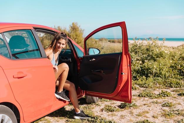 Mädchen, das ein auto verlässt und kamera betrachtet