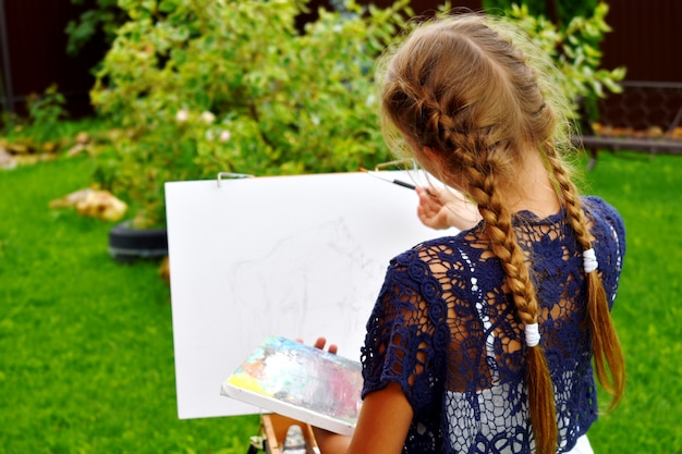 Mädchen, das ein bild auf einem skizzenbuch im freien malt