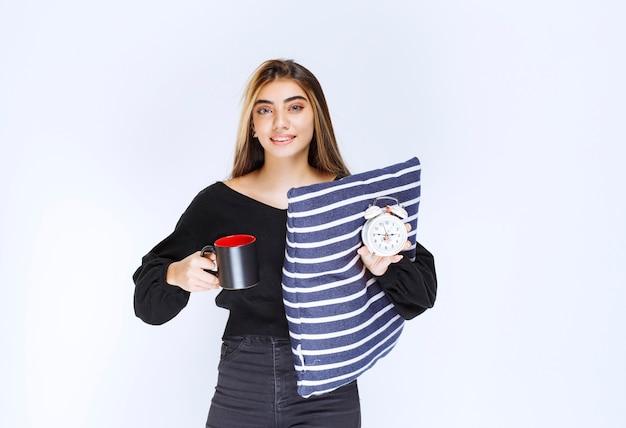 Mädchen, das ein blaues kissen und eine tasse morgenkaffee hält.