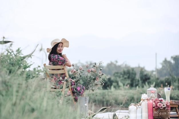 Mädchen, das ein blumenkleid sitzt in der natur trägt