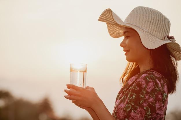 Mädchen, das ein blumenkleid und einen hut hält ein glas wasser trägt