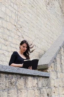 Mädchen, das ein buch an einem windigen tag liest