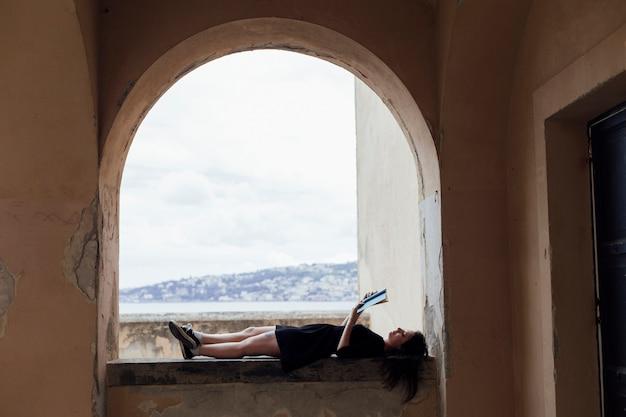 Mädchen, das ein buch auf einer horizontalen lage liest
