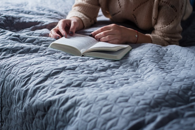 Mädchen, das ein buch auf grauem gemütlichem bett liest. home konzepte.