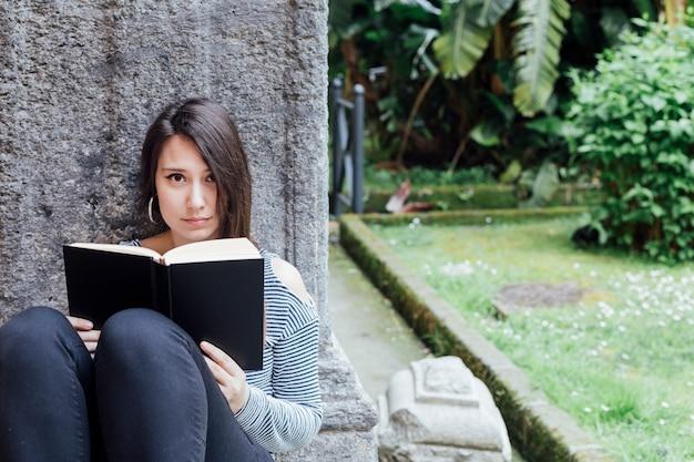 Mädchen, das ein buch im garten liest