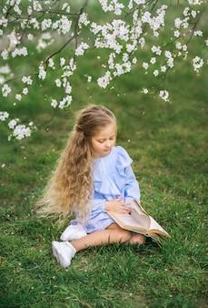Mädchen, das ein buch in der natur liest. blühender garten, frühlingsfoto
