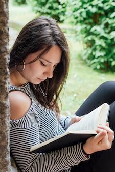 Mädchen, das ein buch in der straße liest