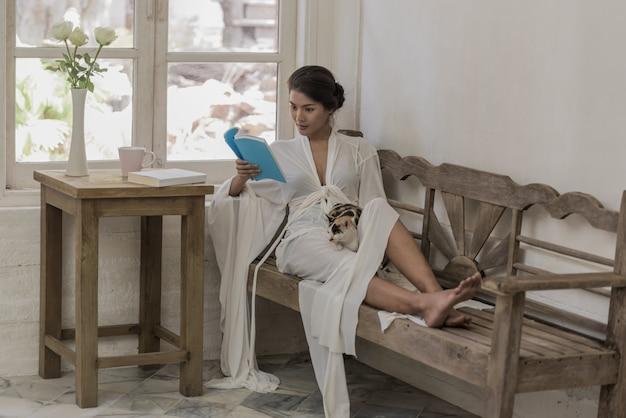 Mädchen, das ein buch mit einer katze auf einer bank im schlafzimmer, entspannendere wochenenden liest.