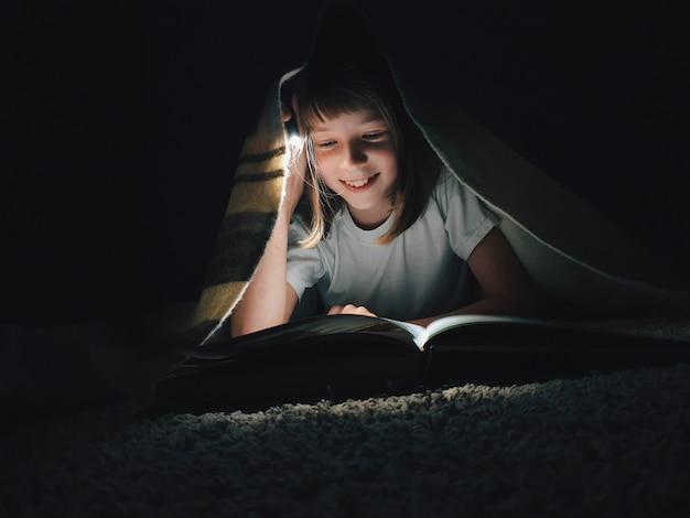 Mädchen, das ein buch mit einer taschenlampe liest