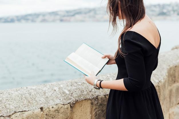Mädchen, das ein buch nahe dem meer liest