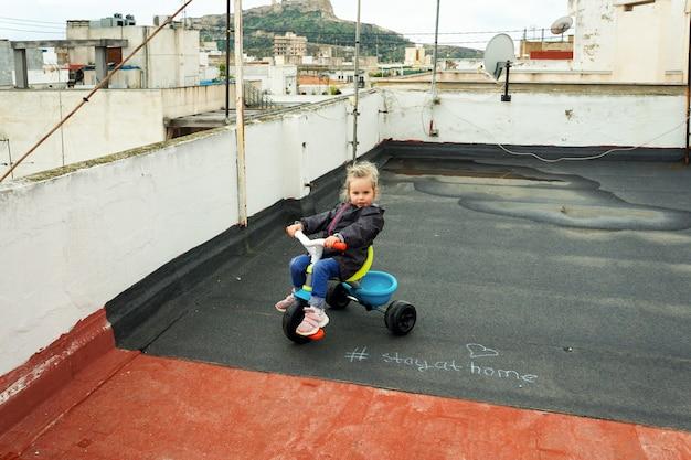 Mädchen, das ein dreirad auf der terrasse eines hauses reitet