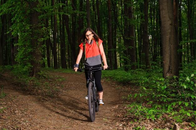 Mädchen, das ein fahrrad im wald reitet
