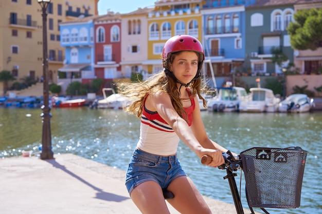 Mädchen, das ein faltbares e-fahrrad in einem hafen reitet