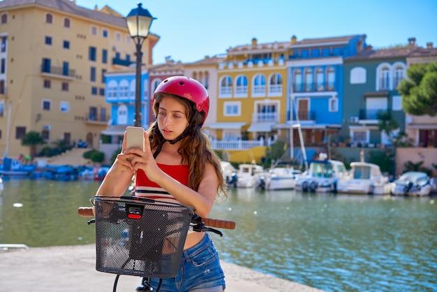 Mädchen, das ein faltbares e-fahrrad in einem mittelmeerjachthafen reitet